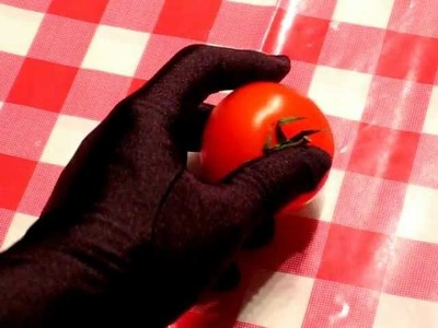 Squeezing a tomato with black satin glove