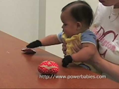 Baby picking up objects using Grabby Gloves from powerbabies.com