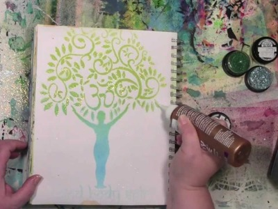 Stencils and spray inks with a touch of glitter in an art journal