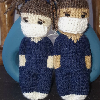Little hand knitted nurse care worker in scrubs and mask
