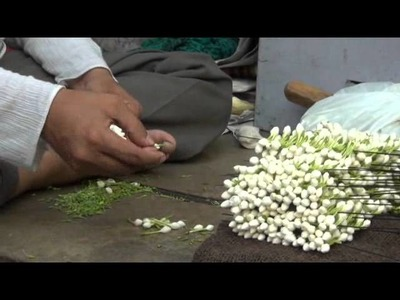 Man putting small flowers in a thread and making mala.