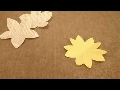 Folding a square piece of paper to cut a five petal flower