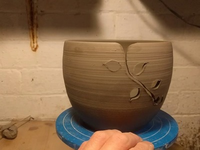 Carving a leaf pattern into yarn bowls. Making handmade pottery in my home studio