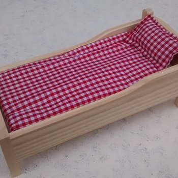 A handmade classic wooden doll's bed complete with gingham bedding.