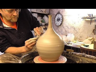 Making. Throwing a Tall Neck Pottery Vase on the Wheel.