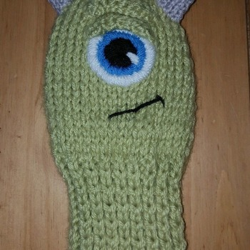 a hand knitted golf club head cover for driver in mikey monsters inc design