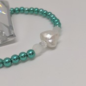Cultured freshwater keshi pearl with teal green and frosted white beads on a stretch elastic thread bracelet