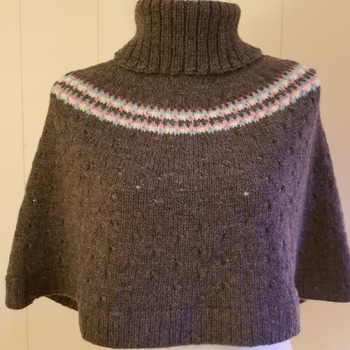 Shoulder cozy wrap made of 100% wool with detailed eyelet design.