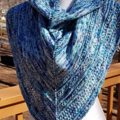 Hand knit sparkly shawl in stelina nylon and merino wool in variegated shades of blue.