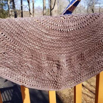 This lovely knit shawl is made of hand dyed 100 percent merino wool. It is lightweight but will keep off the chill beautifully.