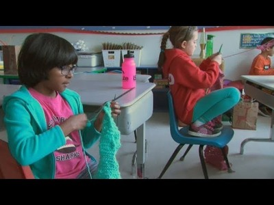 Young students learn to knit warm scarves for the homeless
