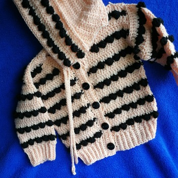Bobble cardigan for babies in a peachy/pink and black , free bonnet